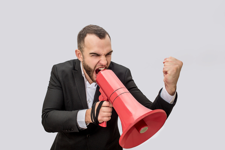 Mad and angry young person scream into red megaphone. He holds it with one hand and show fist with another one. It looks like threat. Isolated on white background. Stock fotó