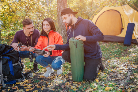 Three friends sit in squad position and look at radio young woman holds. Bearded guy holds sleeping bag. Another young man has knife in cover. They talk.