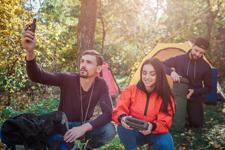 Picture of young beautiful woman holds radio in hands. First guy has satellite phone. Another gets sleeping bag from cover. Stock Photo