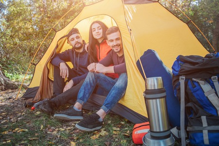 Three friends sit in yellow tent and look outside on backpack. They smile a bit. People are in safe place. Stock Photo