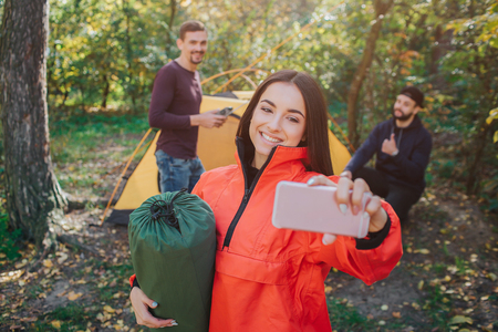 Picture of beautiful young woman takes selfie and smiles. She holds sleeping bag. Young men on back poses as well. They work with tent.