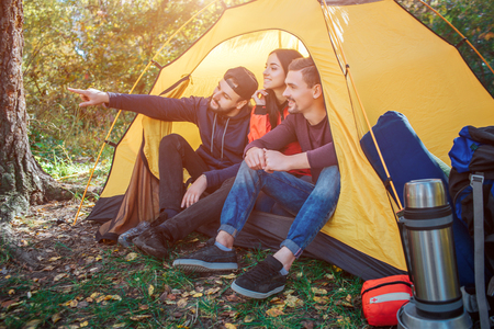 Three friends sit in tent. First young man points forward. Other tow people look in that direction. There is backpack with equipment.
