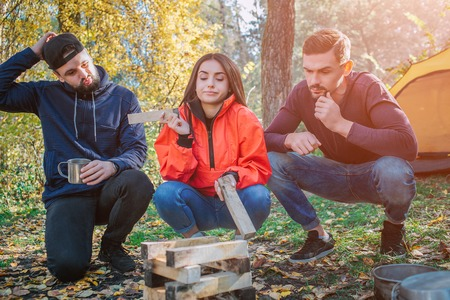 Three friends sitting in squad position and look at brickets of wood. Young woman hold one piece of it. They dont know what to do with it. People are frustrated.