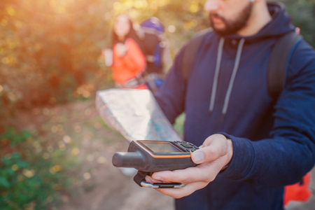 Picture of young bearded man holding satellite phone in hand. There is map in another hand. Young woman stand behind him. She has backpack.