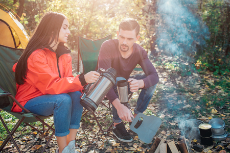 Young woman sit on folding chair and poures hot water from flask into mans cup. She does it accurate. Guy hold thermocup in hand. They sit at fire together.
