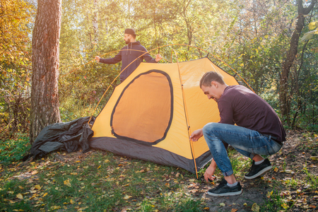 Picture of two young men in forest putting tent. One guy works with ropes. Another stand behind tent. They work together.