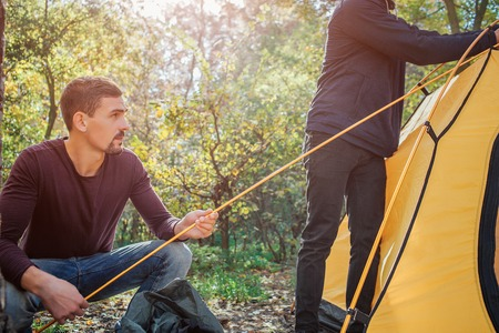 Cut view of two men working. First holds rope while another touches tent. They are in forest.