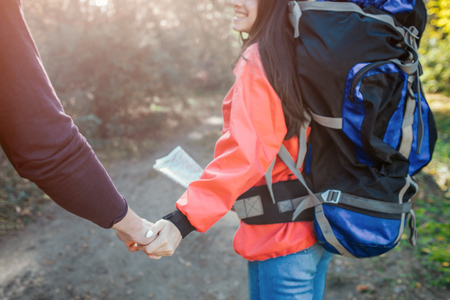 Lovely picture of young man and woman holding hands together. She has backpack on back and map on hands. They walk together.
