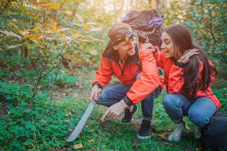Happy couple sitting in squad position in green forest. THey found mushroom. Guy holds machete in hand. He points on mushroom .Young woman is happy Stock Photo