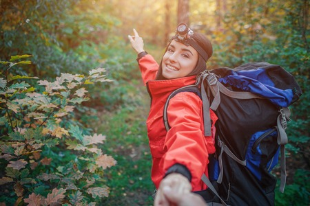 Pictre of cheerful young woman travel in forest. She carry backpack on back. Young woman hold camera and point forward. She smiles