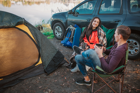 Cheerful young man and woman sit together on folding chairs and look at each other. They hold cups in hands. Young woman covered with blanket. They sit at car and tent with equipment