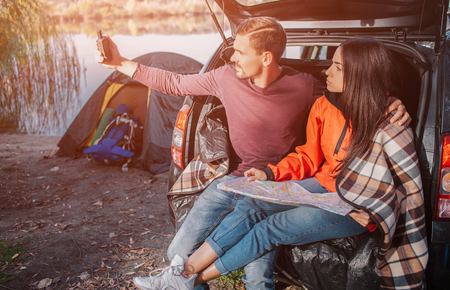 Young man tries to catch signal on his satellite phone. He looks at it and hold in hand. Young woman has map on her nap. She look at phone as well. Couple is serious Stockfoto