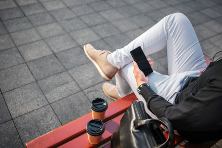 Cut view of man in jeans sitting on bench outside and hold black phone. There re two cups and leather bag.