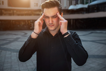 Young man stand outside and hold fingers on plummet. He keeps eyes closed. It is sunny outside. Stock Photo