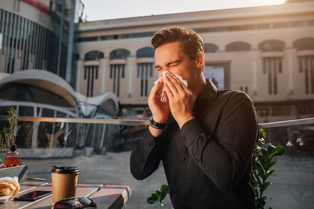Sixk young man sit at table and sneezing in white napkin. He keeps eyes closed. Guy suffer. He sits outside. It is sunny. Stock Photo
