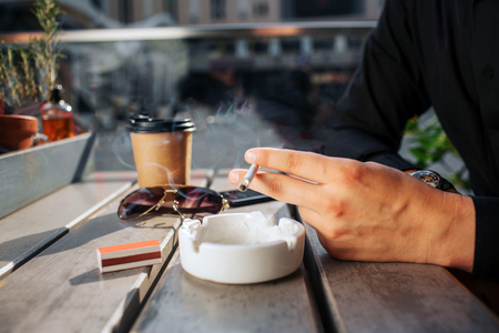 Close up of mans hands hold cigarette in hand. He has it above white plate. There are glasses and cup of drink on talbe. It is sunny outside.