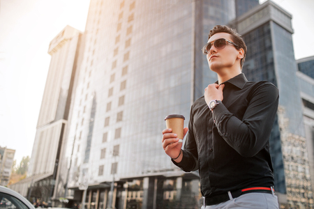 Serious young mn holds hand on collar of shirt and look forward. He has cup of drink. Guy stands in front of skyscrapers.