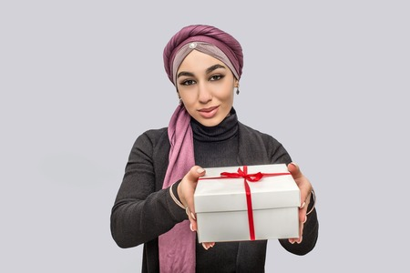 Nice young arabian woman hold present in hands. She looks on camera. Model wears hijab. Isolated on grey background.