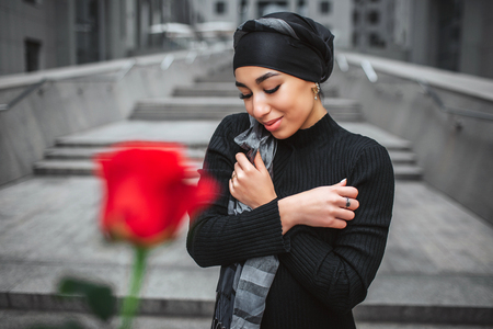 Cheerful young arabian woman poses. She stands on stairs and look down. There is red rose in front of camera. It is unfocused. Model hold hands crossed.