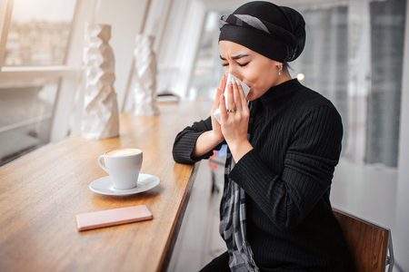 Sick young arabian woman sit inside in cafe. She sneezes in white napkin. Woman suffer. There are cup of coffee and phone at table. Imagens