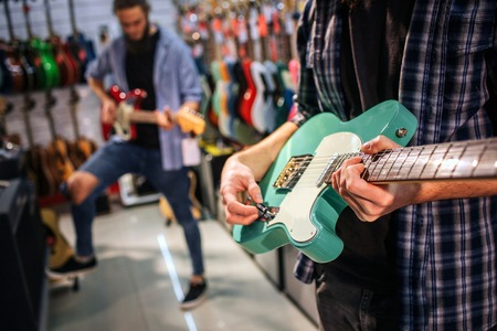 Cut view of two young men playing on electric guitars. First one hold green one. Second guy hold brown guitar and has one leg higher then another. 版權商用圖片