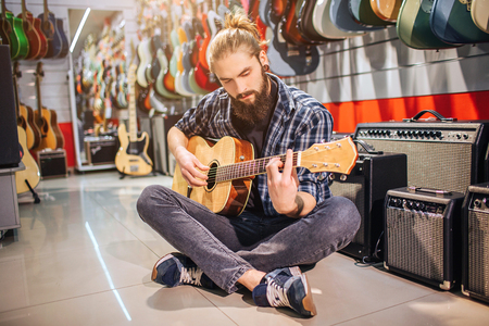 Calm and concentrated young man sit on floor with legs crossed. He playes on acoustic guitar. Many electric guitars and sound speakers are in room. Guy sits alone.