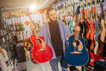 Picture of young hipster stand and hold two colorful acoustic guitars. They are red and dark-blue colors. Guy look at second one. Man electric guitars are behind him. 写真素材