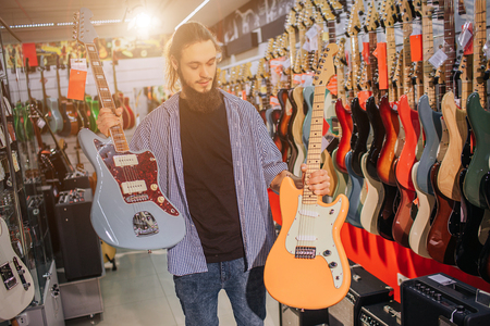 Young man hold two colorful electric guitars. He looks at yellow one. Many other electric guitars are behind him. He stand alone in msuic shop.