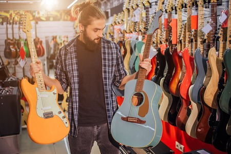 Young bearded guy stand and hold electric and acoustic guitars. He looks at blue one. Young hipster in alone in room full of guitars and different equipment.