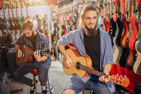 Picture of happy hipster sit on stool and smiling. He hold acoustic guitar in hands. Another young man sit and play as well. He is more concentrated on playing then another one.