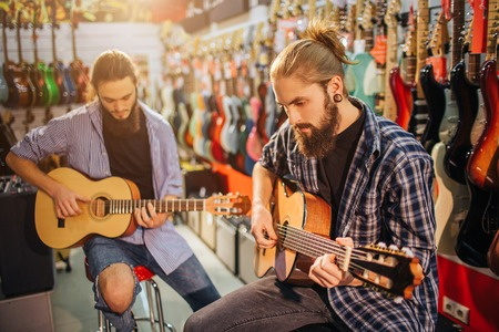 Two concentrated young man playing on acoustic guitars. They sit on stools in room full on electric guitars. Bearded guys play together.