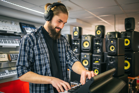 Nice and happy young hipster stand and play on keyboard. He looks down. Guy wears black headphones. Many sound speakers are on right side of room.