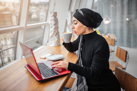 Beautiful and well-dressed young arabian woman drinks coffee and works on laptop. She sits at table inside. It is sunny outside.