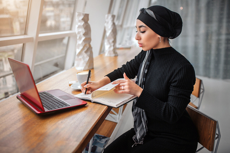 Concentrated arabian woman in black dress and hijab. She sits in side at table and white down in notebook. Laptop and cup of coffee are on table. 스톡 콘텐츠