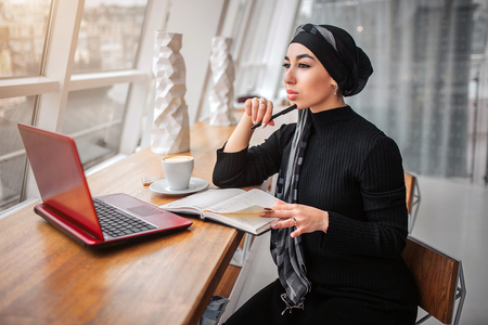 Thoughtful young man sit at table in cafe near window. She looks at it. Arabian woman hold pen in hand. There are notebook. laptop and cup of coffee on table.