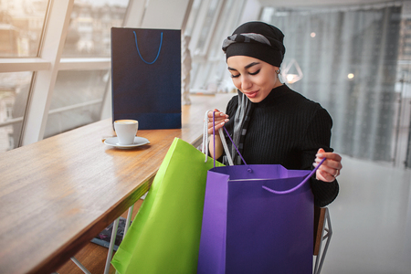 Happy satisfied arabian woman sit inside. She holds shopping bags and look inside of them. Model wear black dress and hijab.