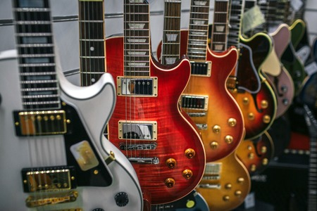 Picture of many electronic guitars hanging. They are different colors and shapes.