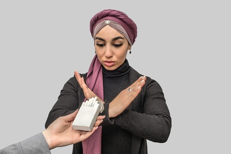 Young arabian woman shows stop sign to cigarettes in small box. Hand holds it. Model looks at box. Isolated on grey background.