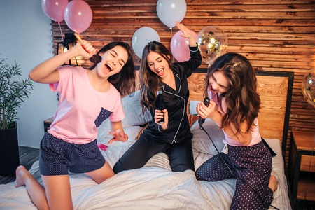 Playful and nice young women stnding on knees on bed in room. They pretend singing in microphones. Models hold makeup brush, spray can and hair equalizer in hands. Reklamní fotografie