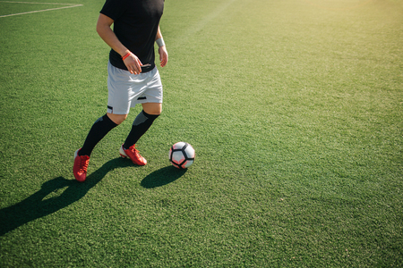 Cut view of man playing footbal alone outside. He is going to kick ball. Stock Photo
