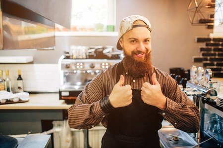 Happy young barista stand and show big thumb up on both hands. He look on camer. Guy stand in kitchen. Light comes out of window. 写真素材