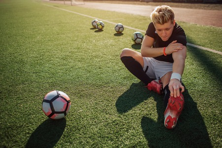 Young blonde football player sit on lawn and stretch. He reaches with one hand to feet. Another one is on shoulder. Four balls behind him and one ball in front.
