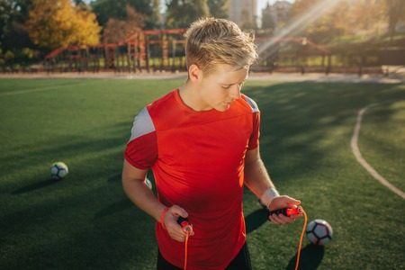 Blonde young man holding jump rope iin hands. He looks at it. Guy stand on lawn outside. Sun is shining. Balls are all around young man. Stock Photo