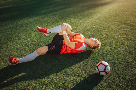 Young football player lying on lawn and hold leg. He pulls it to himself. Guy feels pain in knee. Ball lying besides him. Imagens