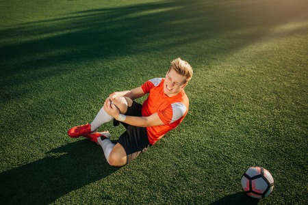 Young football player lying on green lawn and hold hands around leg. He got trauma. Guy feels terrible pain. He suffer. Imagens