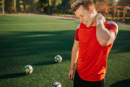 Young player feels pain in neck. He hold hand there and shrinks. Guy stand on lawn. Balls are behind. Weather is good and sunny. Imagens