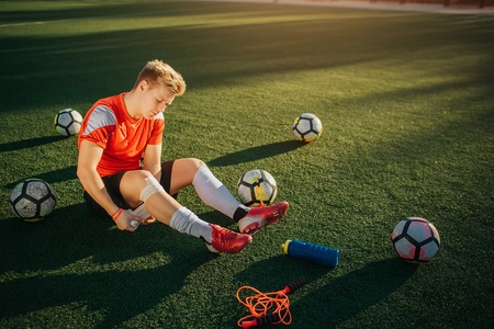 Young player sitting on lawn and wind around leg with bandage. He does it careful. Guy is surround with balls. Theere are bottle of water and jump rope on lawn.