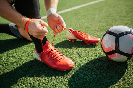 Picture of man lacing soccer sneaker on one leg. He stand on knee. Another sneaker is besides. Ball for game lying on lawn. Close up. Cut view. Stockfoto
