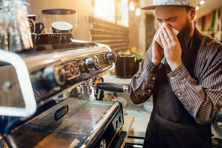 Sick young bearded batista stand at coffee machine and sneezing into white napkin. He is alone in kitchen.