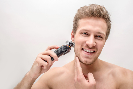 Cheerful young man shaving with machine. He smiles and touches chin. Isolated on white packground. Stock Photo